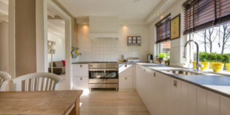 big kitchen with white cupboards and a window