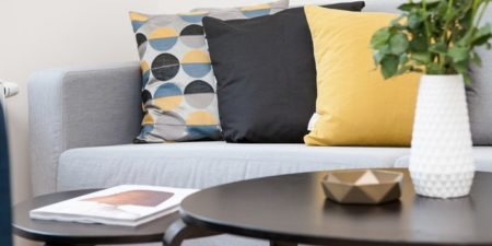 grey couch with yellow pillows