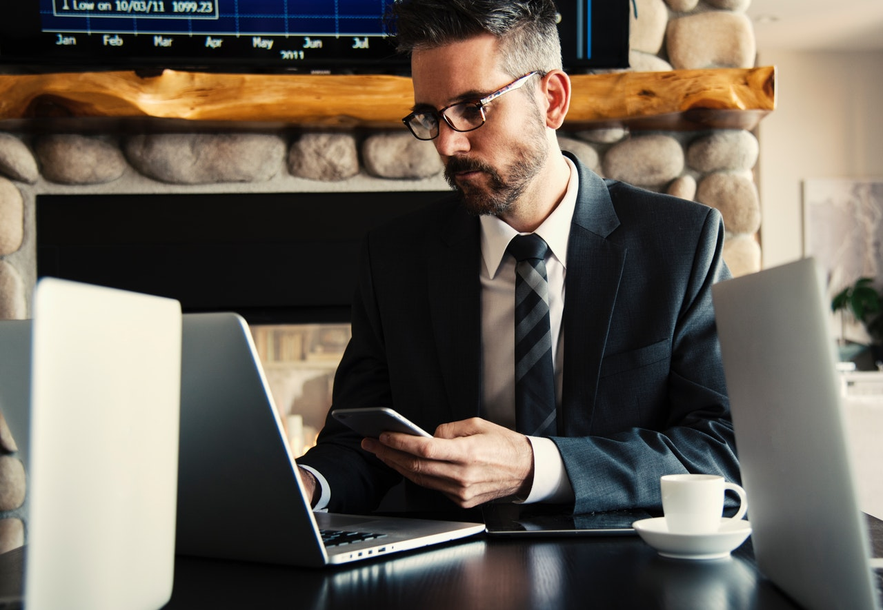 man in suit on computer holding phone