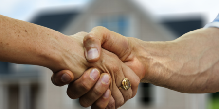 handshake between 2 people with a house in the background
