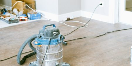 Shopvac vacuum on a dusty wood floor